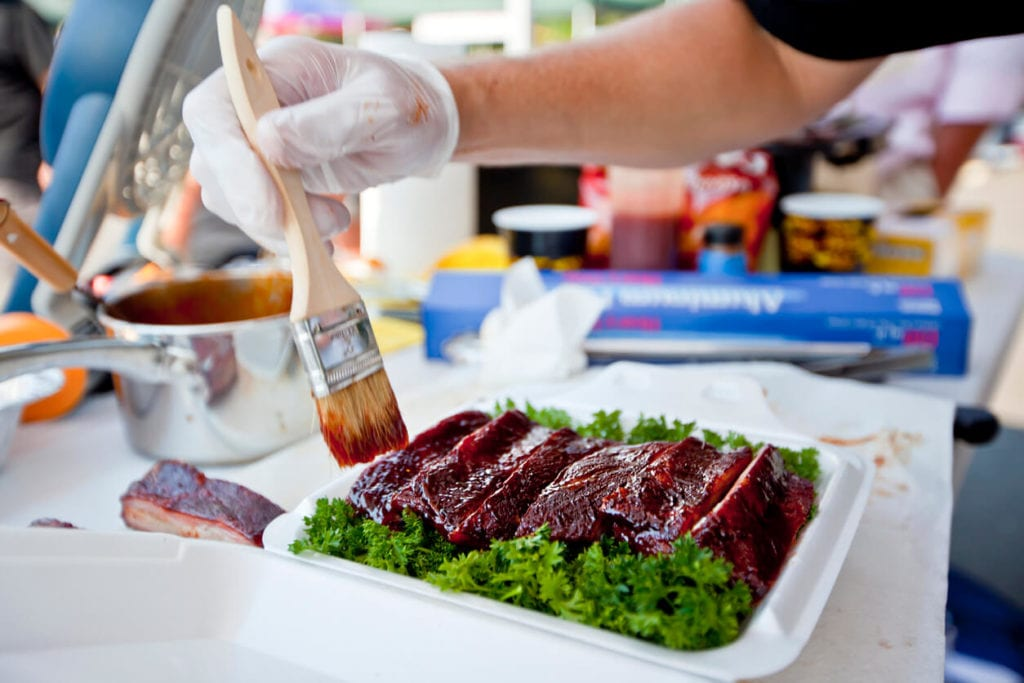 BBQ sauce being brushed on ribs in a food container.