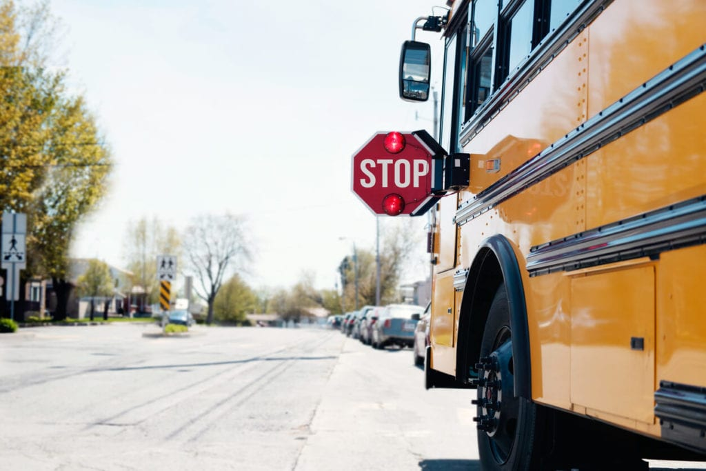 School bus stopped with stop sign present