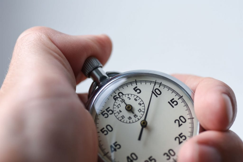 close up of a stopwatch with a thumb on the start button