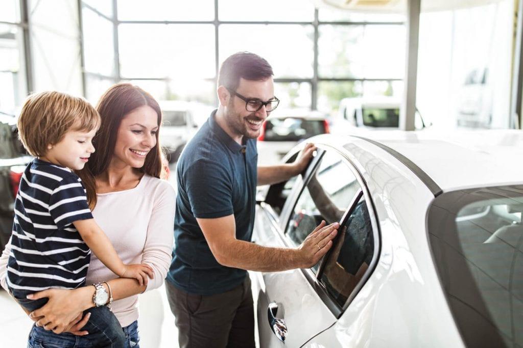 happy family looking at white car at dealership