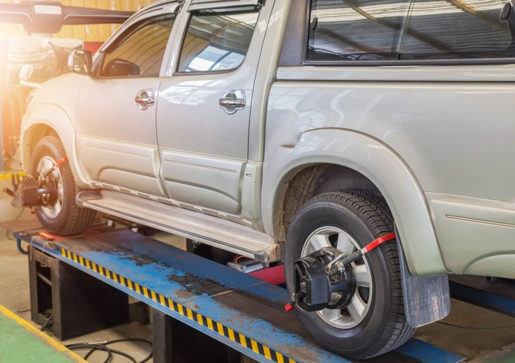 gray pickup truck getting wheel alignment service at service center