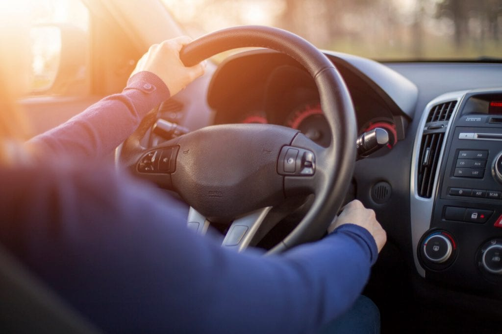 hand on a steering wheel of a car