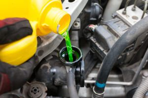 yellow bottle pouring green coolant into car radiator