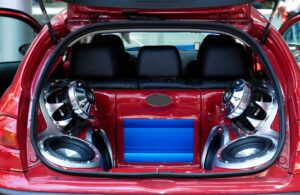 music big loudspeakers installed in a red car's trunk